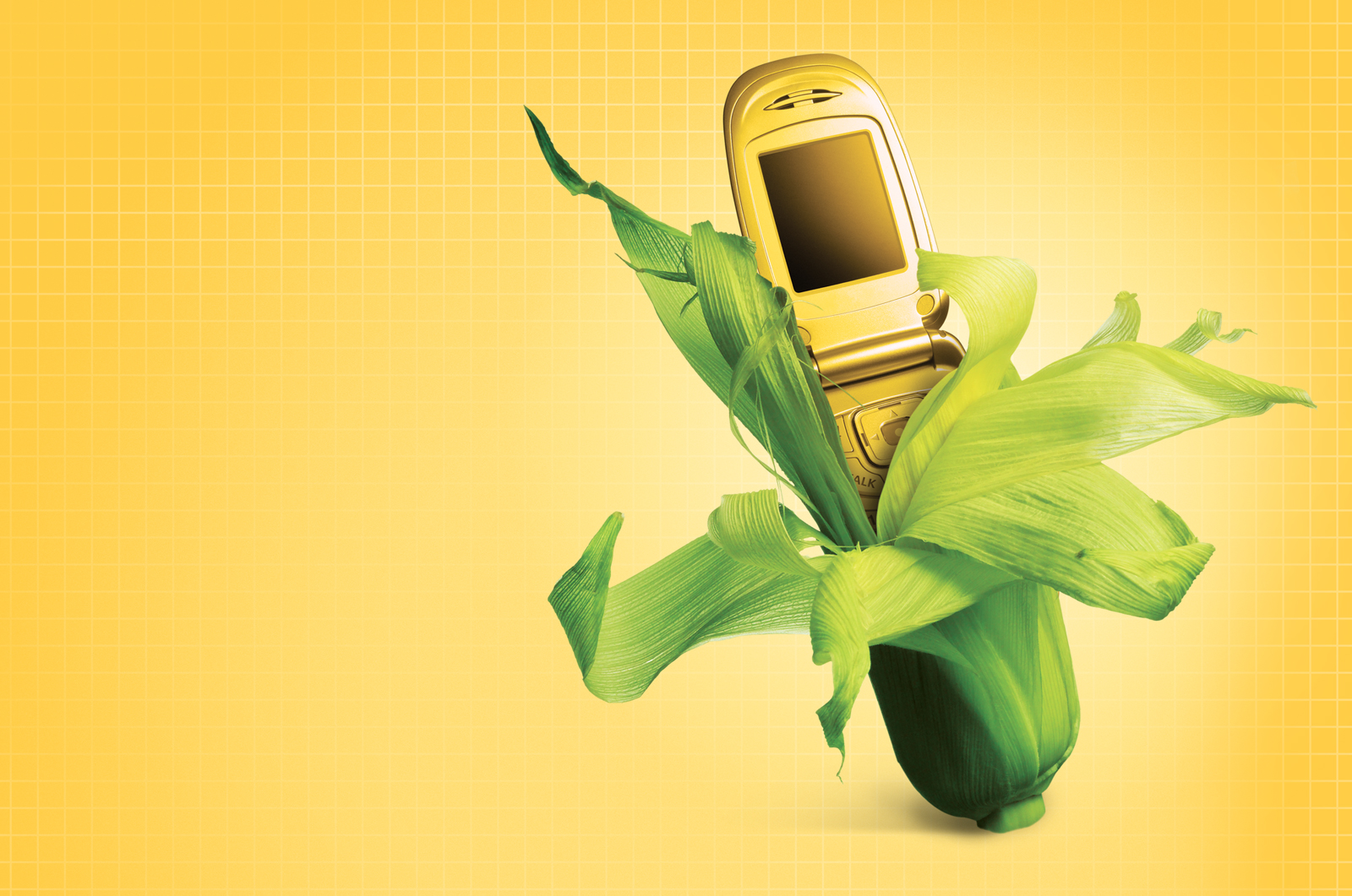 A corn stalk with a yellow tinted cell phone growing out of the green stalk.